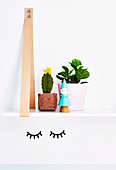 Hanging shelf with crochet cactus and houseplant above the wall sticker