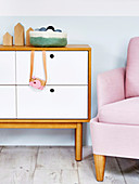 Toy camera hangs on chest of drawers with white drawers