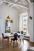 Verschiedene Stühle um einen modernen Esstisch