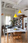 Blick vom Esstisch mit verschiedenen Stühlen ins Wohnzimmer
