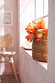 Basket of orange parrot tulips on windowsill