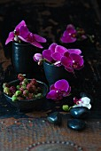 Pink orchids and unripe blackberries in black bowls