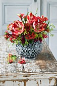 Red and green bouquet of amaryllis, lady's mantle and coral-shaped flowers