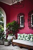 Sofa and plants on a veranda with a pink wall and window grilles