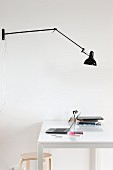 Black anglepoise lamp above white desk