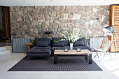 Dark sofa against stone wall