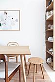 Verschiedene Holzstühle und ein Hocker um den schlichten Esstisch
