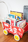 Retro wooden dolls' pram used to hold books
