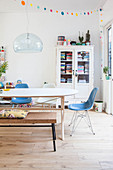 Dining table, chairs and bench in front of vintage bookcase