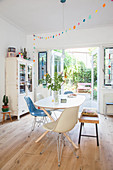 Dining table, chairs and bench in front of vintage bookcase next to terrace doors