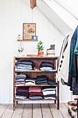 Offenes Regal mit Kleidungsstücken und Kleiderständer im Dachraum mit Holzdielenboden