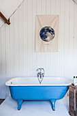 Blue vintage bathtub against white wooden panelling