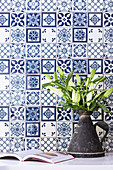 Bouquet of lilies in an old tin can in front of blue and white tiles