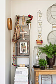 Ladder with ethnic accessories next to a console table with fern
