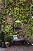 Mirror above the bench on the brick facade with wild wine