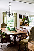 Wicker chairs and upholstered chairs around the wooden table in the rustic dining room