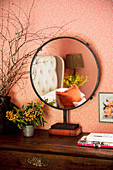 Round standing mirror in the bedroom with patterned wallpaper