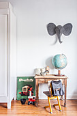 Globe on child's table with cantilever chair below felt elephant head on white wall in child's bedroom