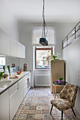 White kitchen counter, upholstered chair and fridge in kitchen with gallery