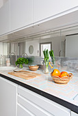White kitchen counter with wooden chopping board, fruit bowl, vegetables and herbs on worksurface