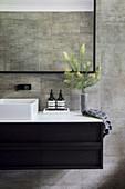 Angular countertop washbasin on black base cabinet