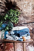 Folded blankets in shades of blue on a wooden table with flowers