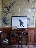 Foto von Sartre vor einer alten Wandmalerei über antikem Sekretär