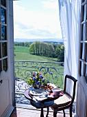 Kleiner gedeckter Frühstückstisch mit Blumen vor dem Balkon mit Ausblick