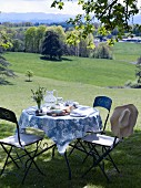 Set garden table on lawn with view over landscape