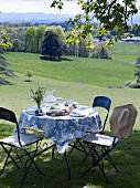 Gedeckter Gartentisch auf dem Rasen mit Blick auf die Landschaft