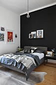 Bed with grey upholstered frame below pictures on narrow shelf on black accent wall