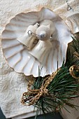 Old Christmas-tree baubles in scallop shell next to fir branch