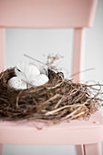 Speckled eggs in Easter nest on pink chair