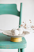Speckled eggs and catkins on plate on green chair