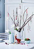 Fabric flowers hung from twigs and white tulips in jug