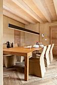 Esstisch mit Hussenstühlen in sandfarbenem Speisezimmer