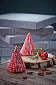 Kleine Tannenbäume aus rot-weißem Papier auf einer Holzscheibe