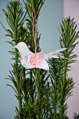 Paper bird hung on yew branch