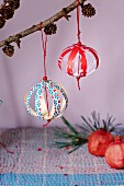 Christmas-tree baubles made from paper strips hung from larch branches