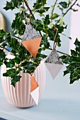 Diamond-shaped paper pendants hung from holly branches in vase