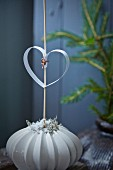 Paper heart on stick in vase with structured surface