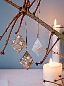 Paper prisms hung from naked fir branch in candlelight