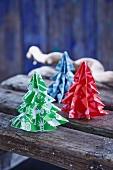 Weihnachtsbäume aus gemustertem Papier auf Holzbrettern