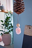 Bauble made from pine cone, wooden bead and paper rosette