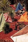 Verschieden gemusterte Tücher im roten Sand zwischen Pflanzen