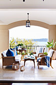 Elegant rattan furniture on a covered veranda with sea views