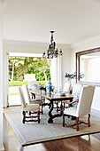Antique French dining table with upholstered chairs on sisal carpet in front of a patio door