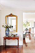 Antique console table with Chinese porcelain, gold frame mirror above