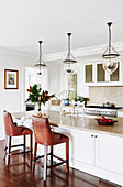 Leather bar stool on the middle block, above it pendant lights with glass shades in an open kitchen