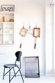 Black classic chair in front of white shelves and vintage utensils on wall